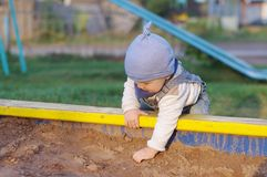 Baby plays with sand on playground. Baby age of 11 months plays with sand on playground Stock Image