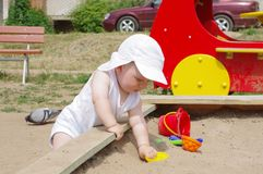 Baby plays with sand on playground. Baby age of 9 months plays with sand on playground Stock Photo