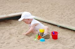 Baby plays with sand on playground. Baby age of 9 months plays with sand on playground Stock Images