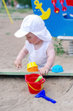 Baby plays with sand on playground Royalty Free Stock Images