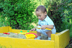 Baby plays in sandbox Royalty Free Stock Image
