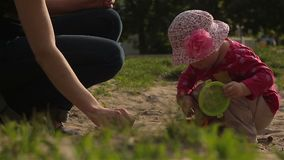 The baby plays in the sandbox. Raises the scoop and pours out the sand. The child plays in the sandbox. Raises the scoop and pours out the sand. Child 16 months stock video