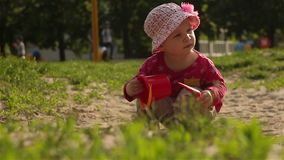 The baby plays in the sandbox. Raises the scoop and pours out the sand. The child plays in the sandbox. Raises the scoop and pours out the sand. Child 16 months stock video footage