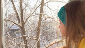 Baby plays sitting on the windowsill on the background of snow-covered trees. stock footage