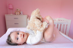 Baby plays with soft toy. Baby (girl age 06 months) plays with soft toy in her bedroom. Concept photo toys and children stock photography