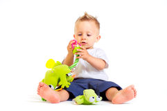 Baby plays with toys. One year old baby boy enjoys playing with toys. Studio Shot. All toys visible on the photo are officialy property released stock photos