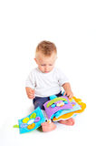 Baby plays with toys. One year old baby boy enjoys playing with toys. Studio Shot. All toys visible on the photo are officialy property released stock photo