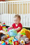 Baby plays toys against white bed Royalty Free Stock Photography