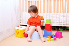 Baby plays toys sitting on potty. Lovely baby boy plays toys sitting on potty royalty free stock photo