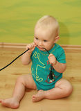 Baby with plug. Curious baby boy playing with plug stock images