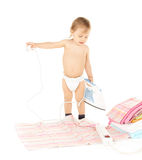 Baby plugging in iron Royalty Free Stock Images