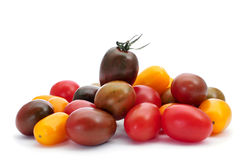 Baby plum tomatoes. Some baby plum tomatoes of different colors on a white background Royalty Free Stock Photography