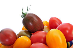Baby plum tomatoes. Some baby plum tomatoes of different colors on a white background Royalty Free Stock Images