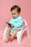 Baby with pocket PC on chamber-pot Royalty Free Stock Photos