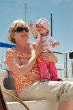 Baby points at sail while sitting on a sailboat Stock Photos