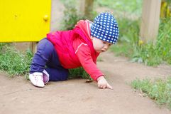 Baby points something sitting on the ground on playground Stock Photos