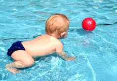 Baby in pool. Full body of a cute little caucasian white baby boy playing with a red ball in the swimming pool outdoors royalty free stock photo