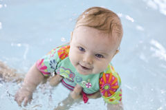 Baby in the pool. Baby girl smiling and having fun in the pool with her mother holding her Royalty Free Stock Photos