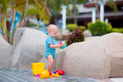 Baby at pool side. Cute little baby boy playing with plastic toy bucket and watering can at pool side in a tropical resort during summer vacation Stock Photo
