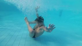 Baby in the Pool Underwater in the Form of an Embryo. Slow motion. In 180 fps. A boy in the form of an embryo dives underwater stock footage