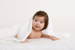 Baby portrait in bed under white towel at studio, yellow toned Royalty Free Stock Photo