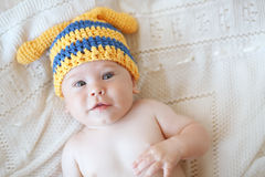 Baby. Portrait of a cute 4 months baby wearing crochet knit hat, top view point Stock Photo