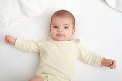 Baby portrait lie on white towel in bed Stock Photos