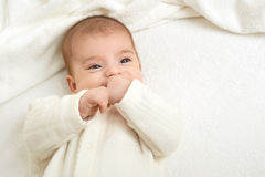 Baby portrait lie on white towel in bed, yellow toned Stock Photography