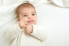 Baby portrait lie on white towel in bed, yellow toned Stock Images