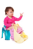 Baby on the pot. Pretty girl is sitting on the pot, holding a roll of paper. on white royalty free stock image