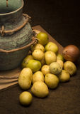 Baby potatoes. And onions are placed on a piece of wood on a dark brown jute material, beside an old green terracotta jug Royalty Free Stock Photo