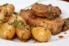 Baby potatoes with roast pork Stock Images