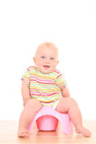 Baby on potty. 10 months baby girl on potty isolated on white royalty free stock photo