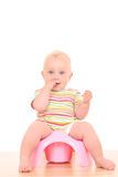 Baby on potty. 10 months baby girl on potty isolated on white stock photography