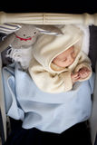 Baby in pram. Newborn child tucked in to a baby stroller with a rabbit soft toy, warm and cuddly with a cardigan with a hood Stock Images