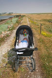 Baby in pram outdoors. Sleeping baby in pram or carriage on countryside track Royalty Free Stock Images