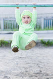 Baby pulls on a horizontal bar Royalty Free Stock Images