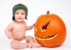 Happy baby boy with carved Pumpkin Royalty Free Stock Photos