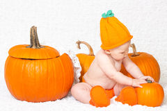 Baby in Pumpkin Hat Sitting near Pumpkins Stock Photography