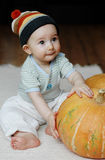 Baby with a pumpkin. Sweet baby sitting on the floor with a big pumpkin Stock Image