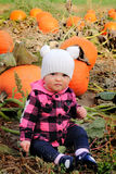 Baby and pumpkins. A cute baby wearing a white knit hat is in a pumpkin patch sitting on the ground innocently looking. Shallow depth of field Stock Photography