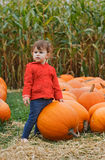 Baby with pumpkins on farm, Halloween Royalty Free Stock Images