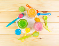 Baby puree in spoon and open banks against the backdrop  pale wood. Stock Photos