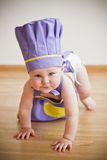 Baby in a purple chief hat and aprons crawling. On the floor at the kitchen Stock Photos