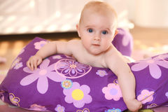 Baby on purple cushion. Portrait of a tiny infant peering over a colorful purple cushion or pillow stock photos