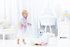 Baby with push walker in white bedroom royalty free stock photography