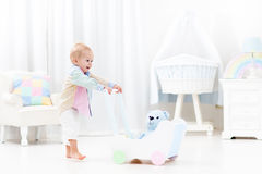 Baby with push walker in white bedroom royalty free stock image