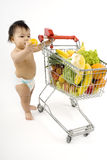 Baby pushes a shopping cart Royalty Free Stock Photography