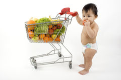Baby pushes a shopping cart royalty free stock image