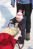 Baby pushing red sledge Stock Photos